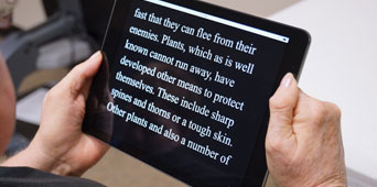 Woman reading iPad with text magnification