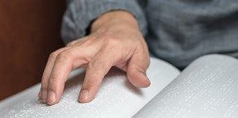 Stock image of hands on Braille