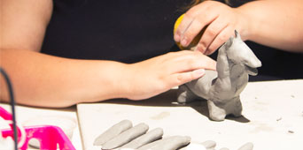 Girl building an animal out of clay